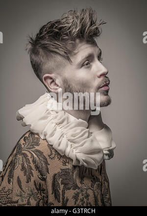 Studio portrait of a young man in profile wearing a jacket with a frilled collar. - Stock Image