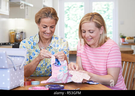 Two Mature Women Sewing Quilt Together - Stock Image