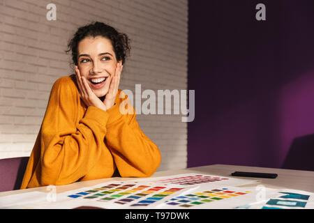 Cheerful artistic woman choosing paint color on a palette indoors - Stock Image