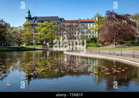 Apartment buildings & Former department store Jandorf and reflection in pond of public park, Volkspark am Weinberg,Mitte, Berlin - Stock Image