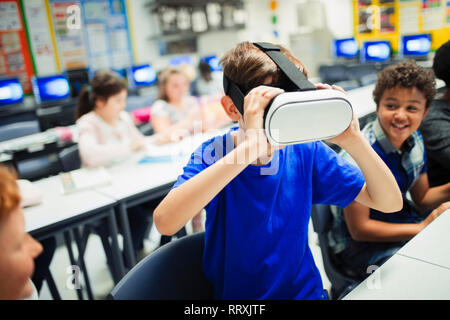 Junior high school boy student using virtual reality simulator glasses in classroom - Stock Image