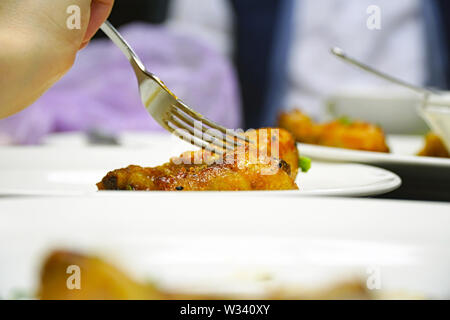 Fork in chicken leg on blurred background. Selective focus - Stock Image