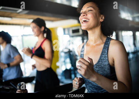 Beautiful fit people exercising together in gym - Stock Image