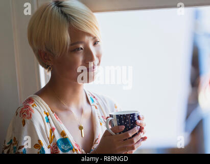 Smiling young woman drinking coffee - Stock Image