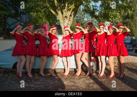 Chichester, West Sussex, UK. 14th Sep, 2013. Goodwood Revival. Goodwood Racing Circuit, West Sussex - Saturday 14th September. The Glamcabs girls dressed in red and gold uniforms salute whilst standing in front of a taxi in the early morning light. Credit:  MeonStock/Alamy Live News - Stock Image