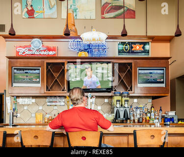 Single man or male customer sitting alone at the bar in a sports bar watching sports on TV in Montgomery Alabama, USA. - Stock Image