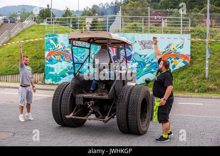 Bielsko-Biala, Poland. 12th Aug, 2017. International automotive trade fairs - MotoShow Bielsko-Biala. Man raising the red-white tape for the Lanz Bulldog tractor. Credit: Lukasz Obermann/Alamy Live News - Stock Image