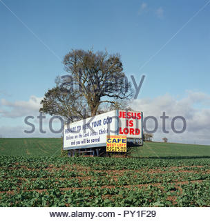 Jesus Is Lord / Barnsdale Bar Cafe - signs on/by old lorry trailer in field adjacent to the A1 trunk road near Skelbrooke in South Yorkshire, UK. - Stock Image