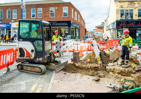 Workmen with a Bobcat excavator digging a trench in the pavement for installation of an electrical power cable - Stock Image