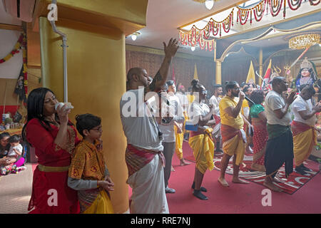 At a Hindu prayer service in Queens worshippers sing and woman blows into a white conch shell. - Stock Image