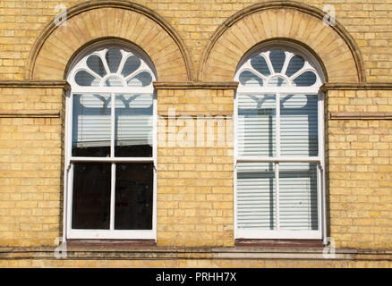 Two Victorian wooden frame white sash window with glass panels on a classic yellow brick wall with white blinders curtains - Stock Image
