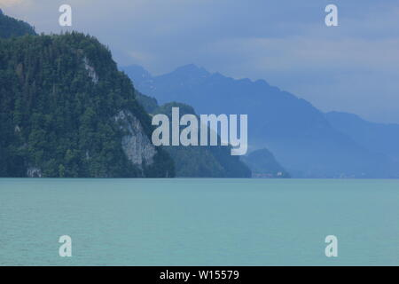Cliff at the shore of Lake Brienz on a rainy summer day. - Stock Image