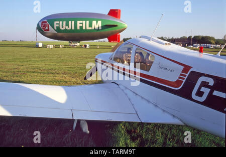 1980s light aircraft at aerodrome airfield with Fuji airship beyond during advertising flights over London for Fujicolor film product Essex England UK - Stock Image