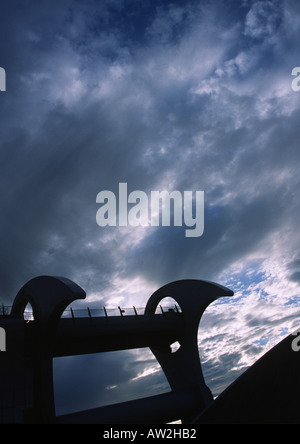 Silhouette of Falkirk Wheel against dark cloudy sky - Stock Image