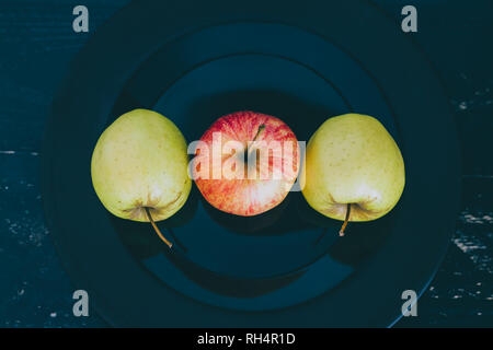 green and red apples on black plate on dark background, concept of choosing the best organic products - Stock Image