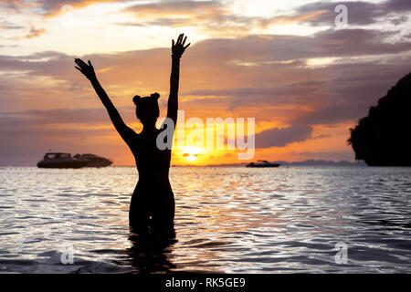 Happy slim girl stands with raised arms at sea beach and meeting sunset - Stock Image