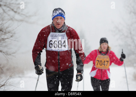 Heavy snow falls as competitors ski in the Mora Vasaloppet. - Stock Image