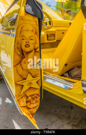 A detail of the back of an open door of a bright yellow Chevrolet lowrider car that has been completely customized including a hand painted portriat o - Stock Image