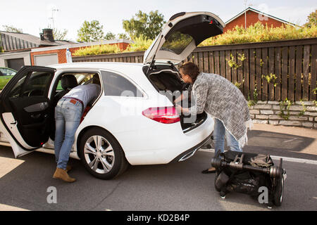 Man and woman packing luggage into car - Stock Image
