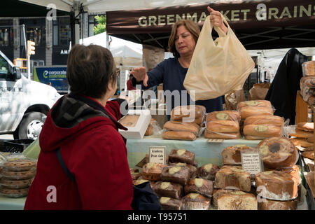 A vendor of bread and pastries making a sale in the Union Square Farmers Market in Manhattan, New York City. - Stock Image