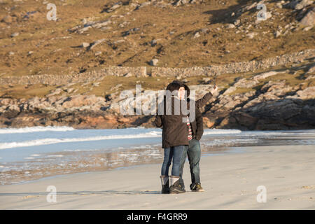 Young couple taking a selfie on a beach - Stock Image