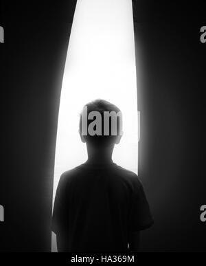 A black and white silhouette of a young boy looking in a bright white window for a hope, dream or faith concept. - Stock Image