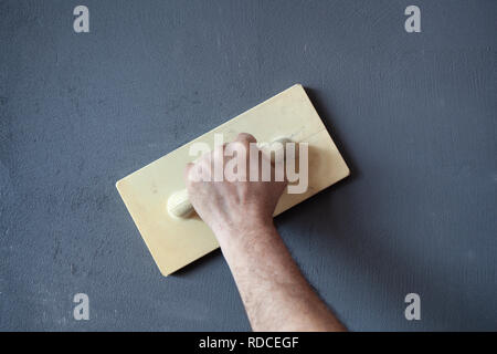 Hand with plastic trowel plastering and smoothing a wet concrete plastered wall. - Stock Image