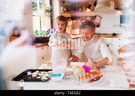 Happy senior great grandmother with small toddler boy making cakes at home. A shot through glass. - Stock Image