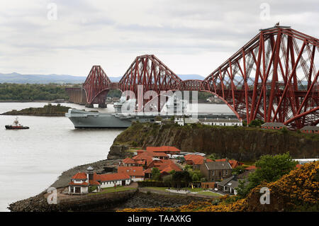 A mast is lowered on the aircraft carrier HMS Queen Elizabeth allowing it to pass under the Forth Rail Bridge as it leaves the Firth of Forth following maintenance at the Rosyth Dockyards. - Stock Image