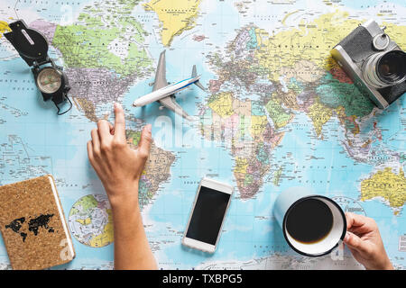 Top view of young woman planning her vacation using world map while drinking coffee - Tourist pointing the next travel destination - Stock Image