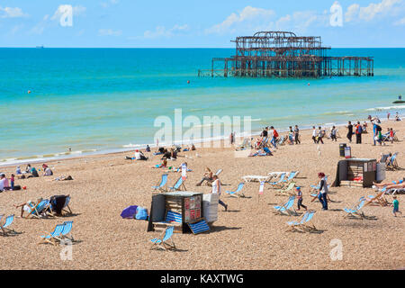Beachgoers enjoy the sun in Brighton, with fire-damaged Brighton's West Pier skeleton in the background. - Stock Image