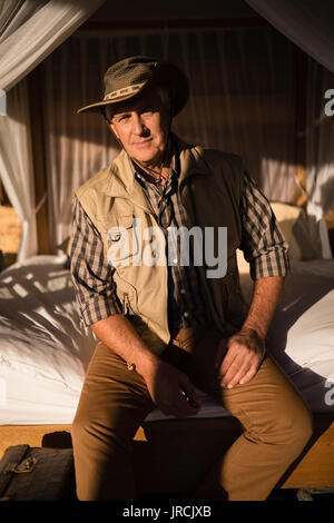 Portrait of smiling man sitting on canopy bed - Stock Image