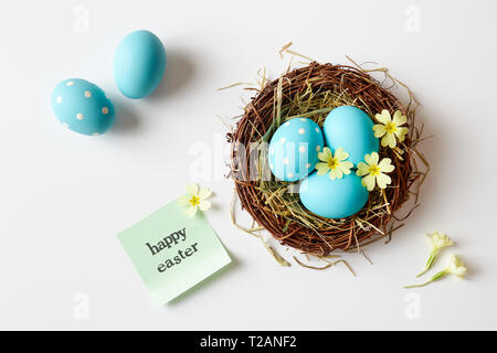 Easter decoration with nest, eggs and spring flowers. Blue Easter eggs in nest with 'Happy Easter' message. - Stock Image