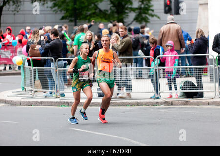 Louzanne Coetzee with her guide runner, competing in the 2019 London Marathon. Louzanne went on to finish 9th in the T11/12 Category, in a time of 03:33:22. - Stock Image