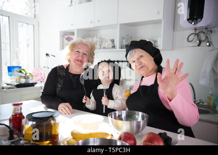 Family eating pancakes and drinking tea in the kitchen. Posing for the camera and waving hands - Stock Image