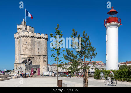 Lighthouse in the port of La Rochelle on the coast of the Poitou-Charentes region of France. The tower with the flag is the Tour de la Chaine which da - Stock Image
