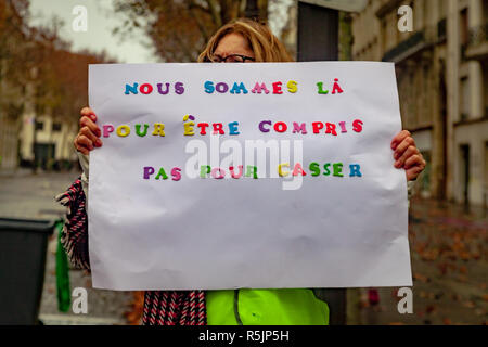 Paris, France. 1st December, 2018.  Woman holding a sign with french text 'We are here to be understood, not to destroy' during the Yellow Vests protest against Macron politic. Credit: Guillaume Louyot/Alamy Live News - Stock Image