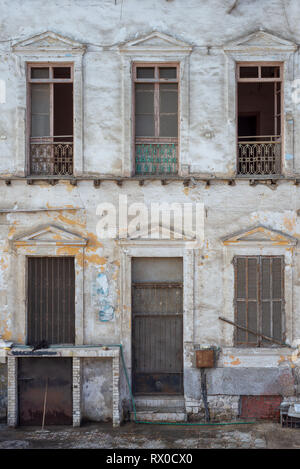 Aged abandoned retro vintage grunge house facade with broken door and windows and weathered shutters - Stock Image