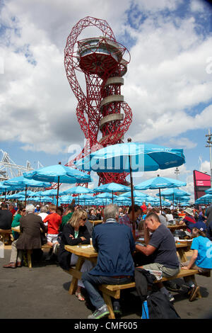 People eating in sunshine outside Orbit sculpture tower designed by Anish Kapoor on a sunny day at Olympic Park, - Stock Image