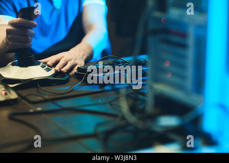 Close-up of unrecognizable gamer sitting at table with computer and cables and using 3D joystick - Stock Image