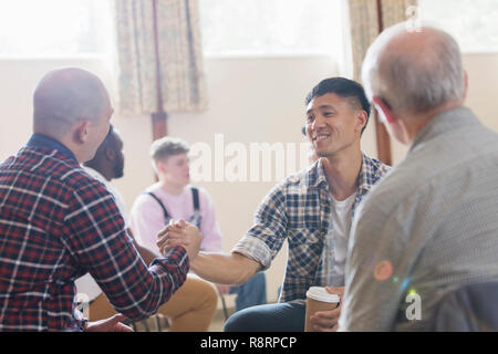Men shaking hands in group therapy in community center - Stock Image