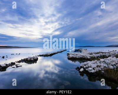 Late afternoon glass-like sea surface seascape with horizon small harbor for fishing boats near Povljana on Pag island in Croatia - Stock Image