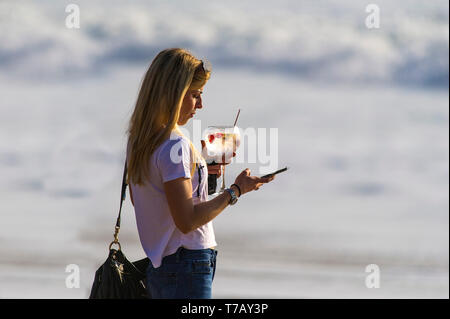 A woman standing in the evening sunlight holding a cocktail and texting on her mobile phone. - Stock Image