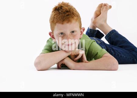 Young boy with red hair and freckles age 7, laying with his feet up. Model Released. Studio shot.       Ref: CRB538_103609_0039  COMPULSORY CREDIT: Ma - Stock Image