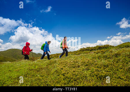 Mom with two kids hiking in mountains - Stock Image