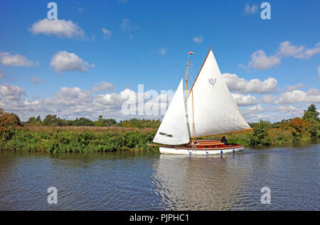 A yacht in full sail on the River Ant on the Norfolk Broads passing by How Hill at Ludham, Norfolk, England, United Kingdom, Europe. - Stock Image