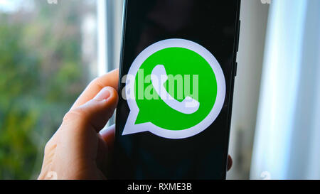 hand use Whatsapp app symbol on smartphone - Stock Image