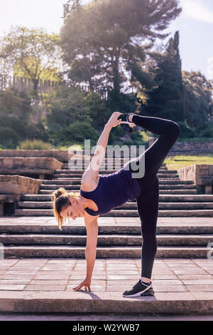 pretty young girl doing yoga exercise on the stairs of the park, morning workout outdoors, sports and healthy lifestyle - Stock Image