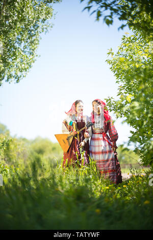 Two young women in traditional russian clothes stand in the field between the greenery - look at each other - Stock Image