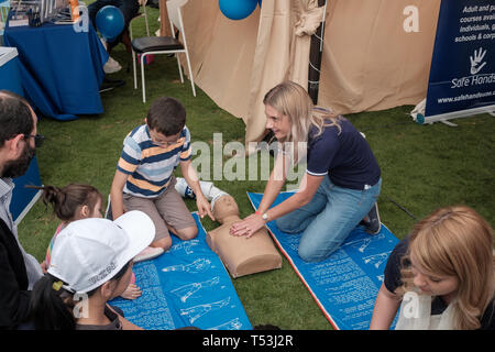 February 22, 2019 - Abu Dhabi, UAE: Young female first-aider demonstrating CPR to kids with dummy kid - Stock Image